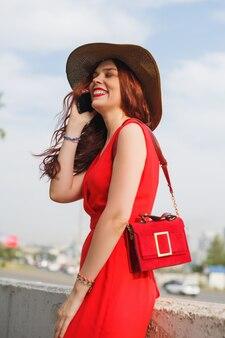 広い帽子をかぶった幸せな若い女性がバッグを持って夏に歩いて電話で話している
