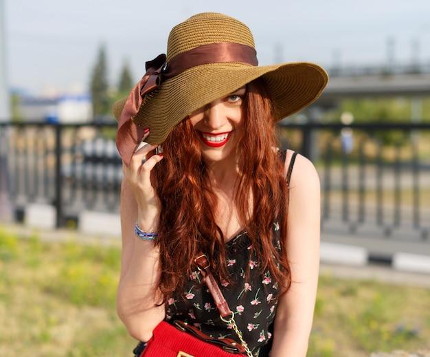 幸せな若い女性は、広い帽子をかぶって、夏に公園でポーズをとる