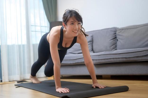 スポーツウェアの幸せな若い女性が自宅の居間で運動しています