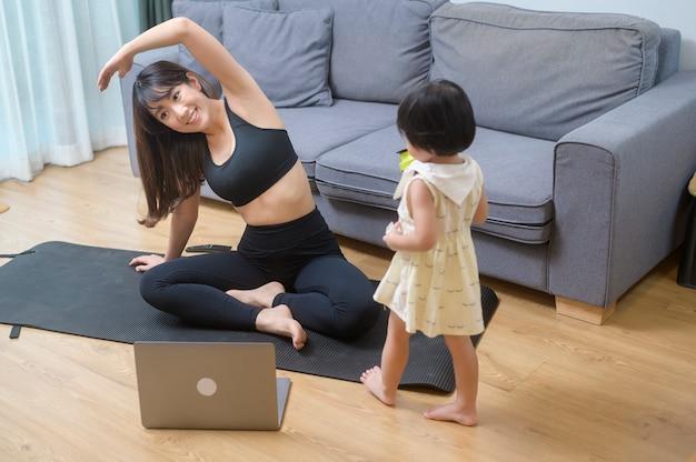 Счастливая молодая женщина в спортивной одежде с дочерью тренируется в гостиной дома
