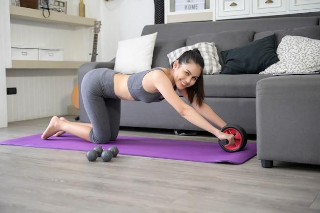 운동복에 행복 한 젊은 여자는 집에서 복부 바퀴 운동입니다