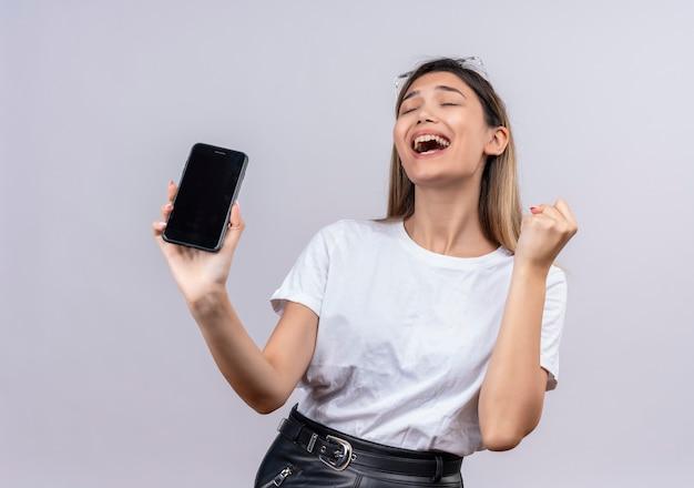 白い壁にくいしばられた握りこぶしで携帯電話の空白を表示しながら笑顔のサングラスで白いtシャツの幸せな若い女性
