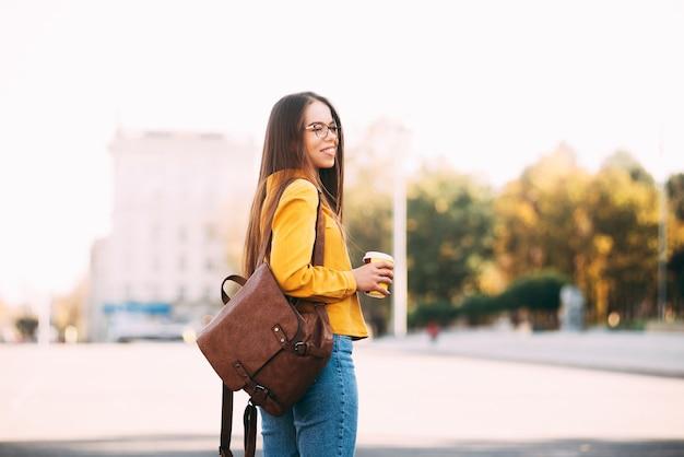 幸せな若い女性が晴れた日に彼女の熱い飲み物を持って通りを歩いています