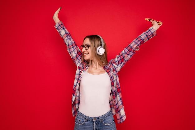 Счастливая молодая женщина слушает музыку в наушниках со своего телефона на красном фоне