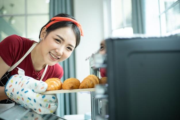 Счастливая молодая женщина вынимает поднос с круассанами из духовки