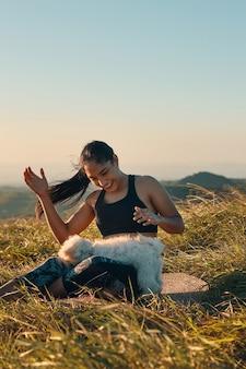 그녀의 아름다운 강아지와 함께 연주 잔디에 앉아 행복 한 젊은 여자