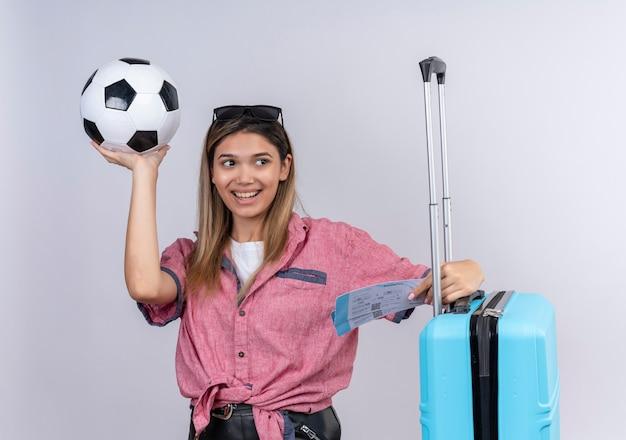 Счастливая молодая женщина в красной рубашке и солнцезащитных очках смотрит в сторону, держа мяч с билетами на самолет и синий чемодан на белой стене