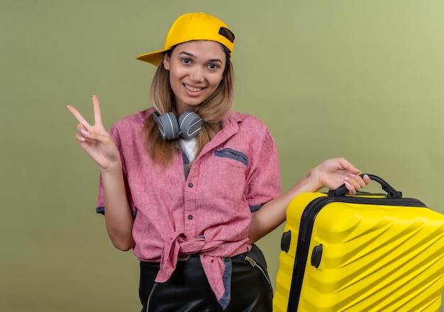 Счастливая молодая женщина в красной рубашке и желтой бейсболке показывает жест двумя пальцами, неся желтый чемодан на зеленой стене