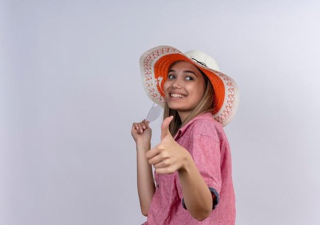 Счастливая молодая женщина в красной рубашке держит билеты на самолет с большими пальцами руки вверх, глядя в сторону на белой стене