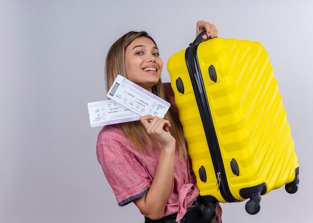 Счастливая молодая женщина в красной рубашке улыбается и показывает билеты на самолет и желтый чемодан на белой стене