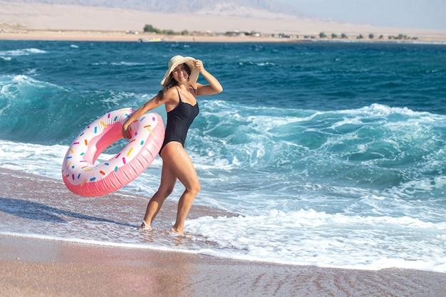 Счастливая молодая женщина с кругом для плавания на берегу моря в форме пончика. концепция отдыха и развлечений на отдыхе.