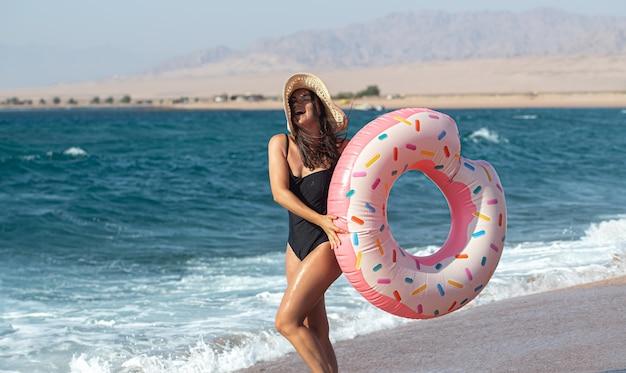 海のそばにドーナツ型の水泳サークルを持つ幸せな若い女性。休暇中のレジャーとエンターテイメントの概念。