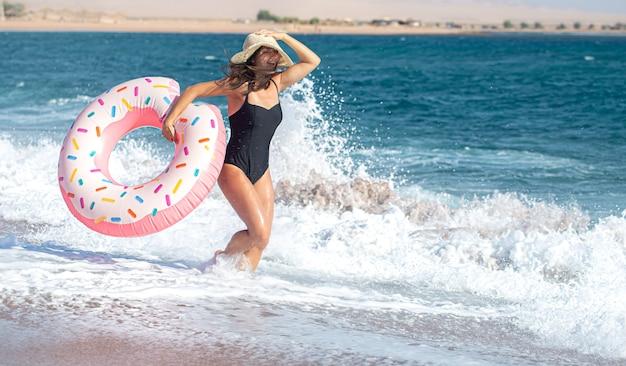 海のそばのドーナツ型の水泳サークルを持つ幸せな若い女性。休暇中のレジャーとエンターテイメントの概念。