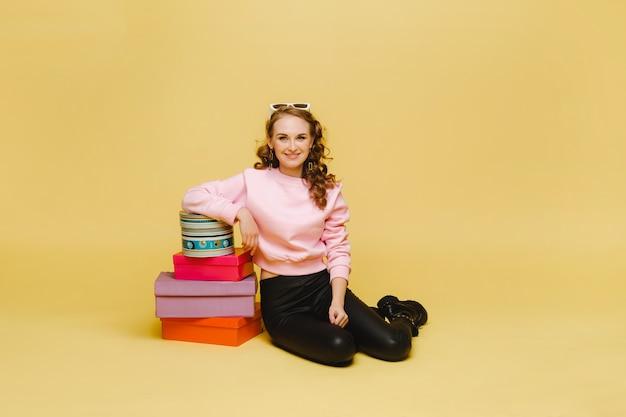 オレンジ色のスタジオの背景に分離された買い物後のカラフルな紙箱を持つ幸せな若い女性。季節の販売、購入、贈り物にお金を使う
