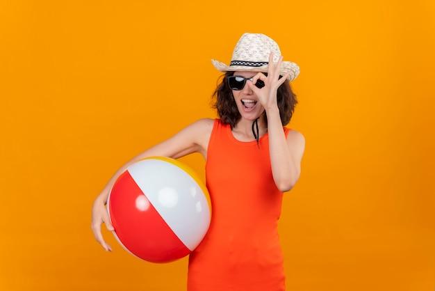 指で作られた穴を通して見ている膨脹可能なボールを保持している太陽の帽子とサングラスを身に着けているオレンジ色のシャツの短い髪の幸せな若い女性