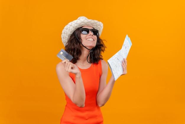 地図とクレジットカードを保持している太陽の帽子とサングラスを身に着けているオレンジ色のシャツの短い髪の幸せな若い女性