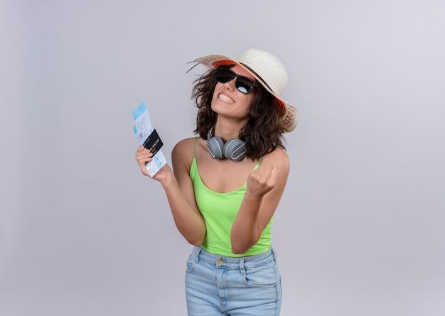 Счастливая молодая женщина с короткими волосами в зеленом топе в шляпе от солнца и солнечных очках с билетами на самолет и кредитной картой на белом фоне