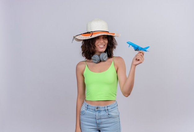 白い背景の上の青いおもちゃの飛行機を保持している太陽の帽子をかぶって緑のクロップトップで短い髪の幸せな若い女性