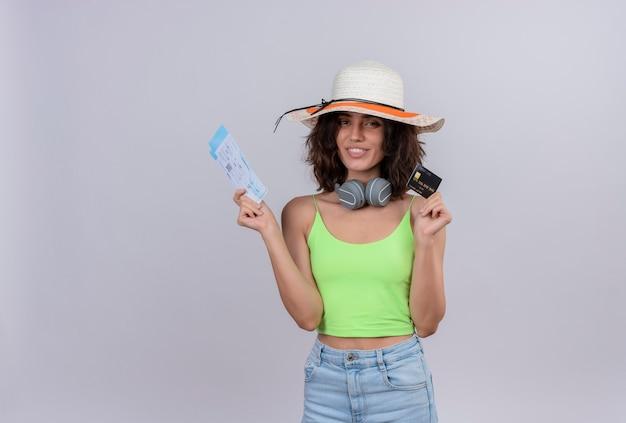 Счастливая молодая женщина с короткими волосами в зеленом топе в шляпе от солнца показывает билеты на самолет и кредитную карту на белом фоне