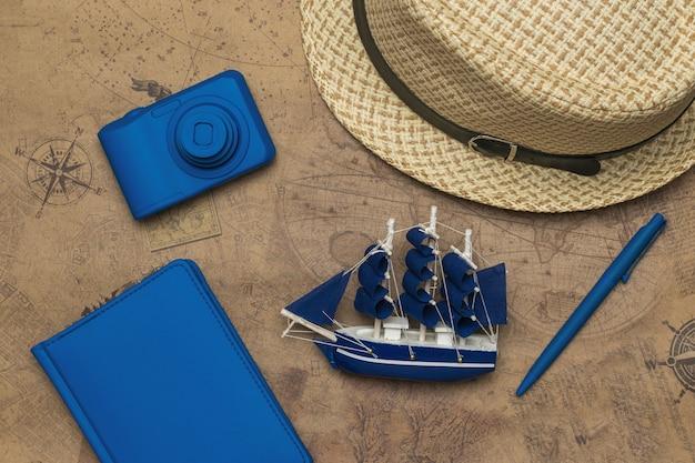 Шляпа, фотоаппарат, блокнот и модель парусника на фоне старой карты. концепция планирования путешествия.