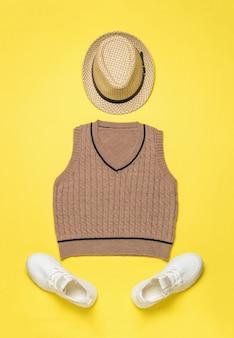 Шапка, вязаный жилет и пара белых кроссовок на желтом фоне. модная классическая вязаная одежда.
