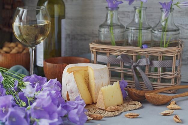 パン、ナッツ、白ワイン、夏の花を添えた新鮮なオーガニックチーズの頭。健康的で有機食品のコンセプト。