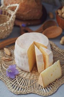Голова свежего органического сыра подается с хлебом, орехами, белым вином и летними цветами. концепция здорового и органического питания.