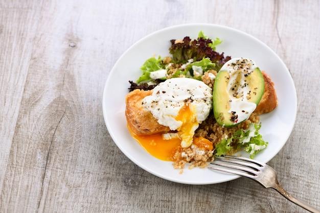 Здоровый и сбалансированный завтрак. яйцо бенедикта намазывается на тосты с половиной авокадо, киноа и салатом, приправленными специями и йогуртовой заправкой.