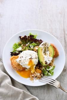 Блюдо для здорового и сбалансированного завтрака. яйцо бенедикта намазывается на тосты с половиной авокадо, киноа и салатом, приправленными специями и йогуртовой заправкой. наслаждайтесь самой важной едой