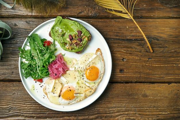 건강하고 균형 잡힌 아침 식사-카망베르, arugula 샐러드 및 아보카도 토스트와 스크램블 계란. 나무