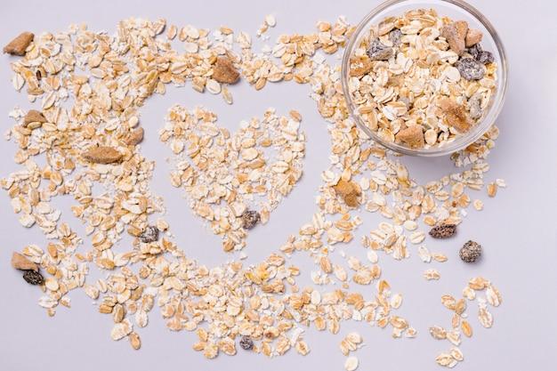 健康的な朝食。白い背景の上のハートの形をしたフレークとドライフルーツ。