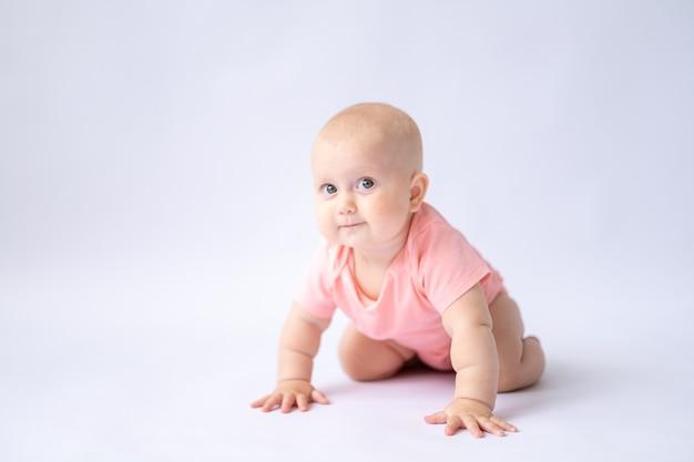 흰색 배경에 있는 건강하고 쾌활한 아기는 카메라 절연체를 들여다본다