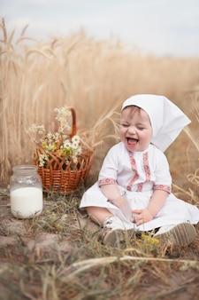 自然と調和した健康な子供時代。民俗服を着た幸せな小さな赤ちゃんは、新鮮な牛乳の瓶と小麦畑に座っています