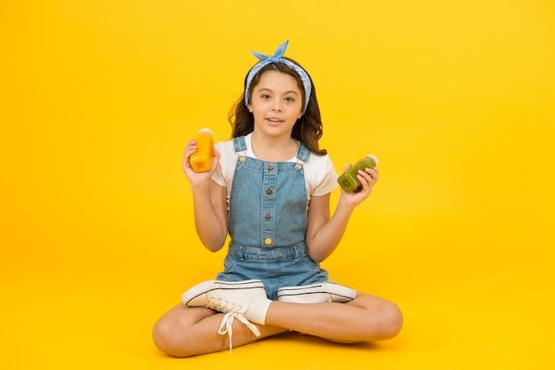 子供のための健康的なダイエット。小さな女の子は、ビタミン栄養のボトルを保持しています。小さな子供は健康的なダイエットを楽しんでいます。成長と発展のための栄養豊富なダイエット。ダイエットの日。