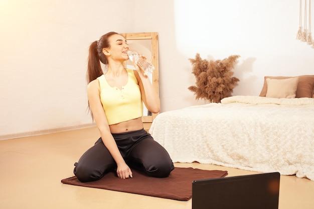 健康的な生活スタイル。女性は水を飲み、運動から休む。朝の充電、ラップトップ