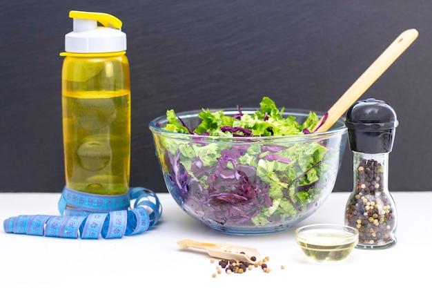 紫キャベツとレタスのヘルシーなナチュラルフレッシュサラダ。食事療法、菜食主義。テーブルの上のテープを測定します。