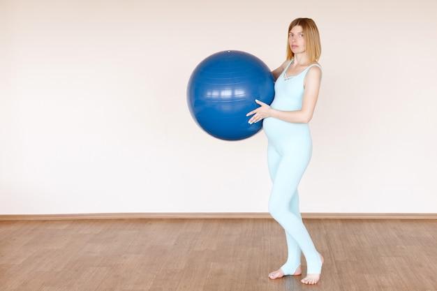 明るいスタジオでフィットネスボールを持った健康な妊婦。妊娠の準備