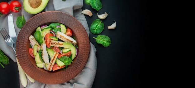 暗い背景に鶏の胸肉、新鮮な野菜、ほうれん草の葉、アボカド、トマトのヘルシーサラダ。肉と野菜のサラダ。ダイエット食品のコンセプトです。コピースペース。ベナーフード。