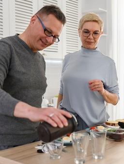 Здоровая спортивная пара пожилых людей принимает протеин из шейкера перед ужином