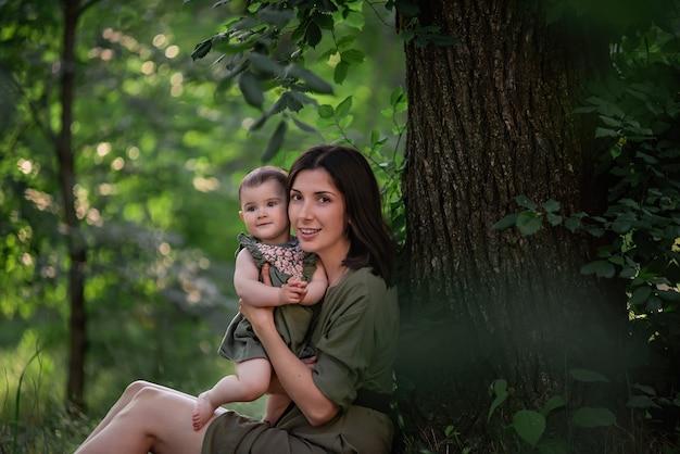 건강한 젊은 어머니는 그녀의 팔에 유아 아기를 보유하고 있습니다. 행복한 가족은 키가 큰 나무 아래 푸른 잔디에 앉아 놀고 포옹합니다.
