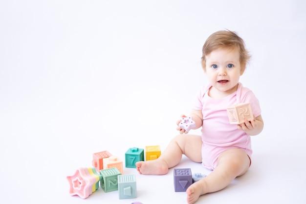 Здоровый милый маленький ребенок в розовом боди сидит и играет с разноцветными кубиками на белом