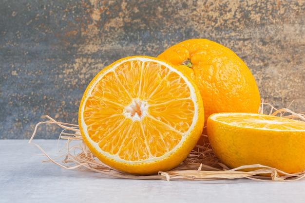 Куча восхитительных апельсинов на соломе, на мраморе.