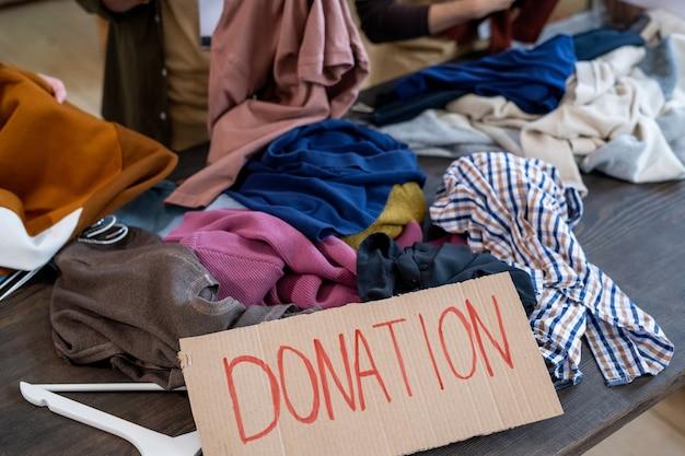 黒い木製のテーブルに寄付の服の山