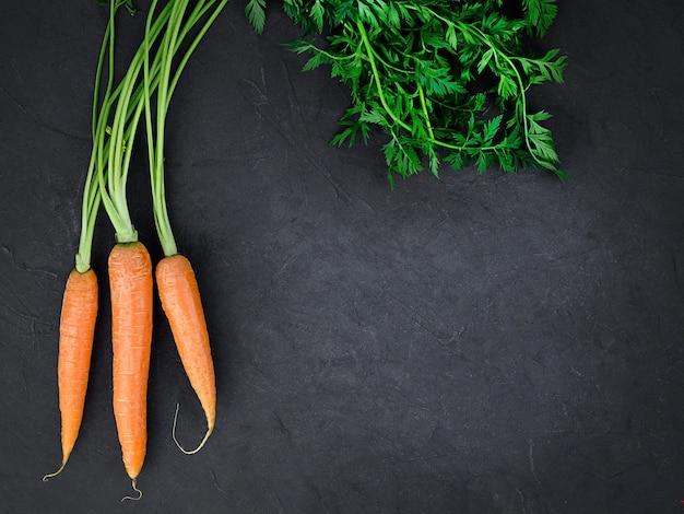 Куча свежей органической моркови на черном фоне. фото высокого качества