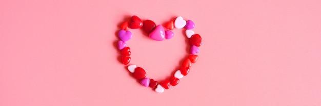 Куча сердца в виде глянцевых бусинок разных оттенков розового цвета, выложенных в форме сердца на розовом фоне. знамя