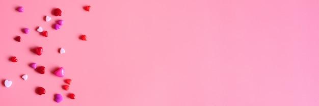 ピンクの背景にさまざまなピンクの色合いのハート型の光沢のあるビーズの山。バナー。テキスト用のスペース