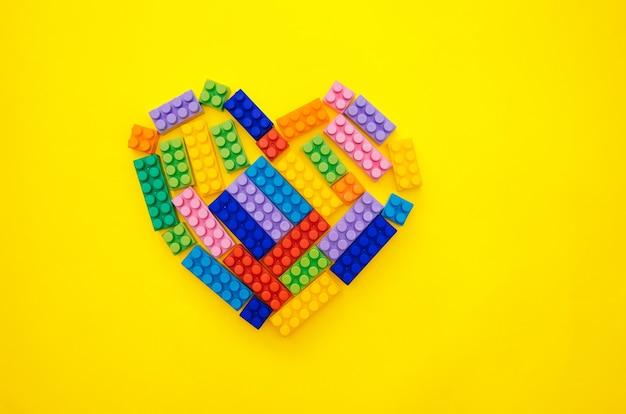 노란색 배경에 어린이 멀티 컬러 생성자의 심장. 텍스트를 위한 빈 공간입니다.휴일 날짜입니다.발렌타인 데이입니다.