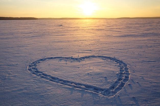 雪の中にハートが描かれています。バックグラウンドでの夕日。