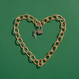 Сердце из золотой цепочки с замком. зеленый фон