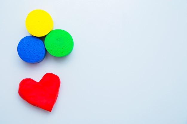 Сверху фото лежит сердечко из красного теста для лепки, а внизу на белом фоне лежат желтые, зеленые и синие кружочки .. фото высокого качества